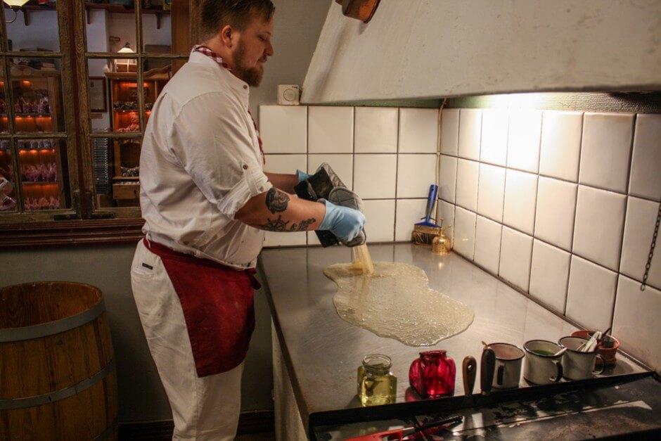 Isaac gießt die Zuckermasse auf die kalte Platte
