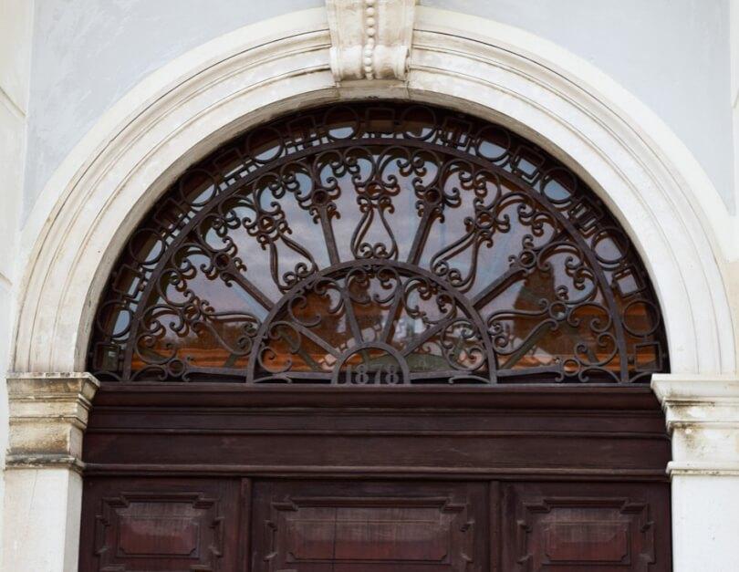 Schmiedeeisernes Oberlicht am Eingang zum Rathaus von Piran, das Fischerdorf an der Adria