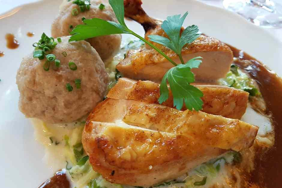 Chicken drumsticks with bread dumplings on a bed of vegetables in the Gasthof Zum Stern