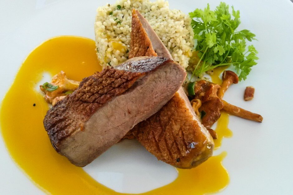 Duck breast on mango vinegar glace with bacon chanterelles and olive bulgur